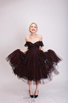 Zbliżenie portret pięknej blondynki przymierzającej czarną puszystą sukienkę, dziewczyna pokazuje jej ładne szmatki. ma upięte włosy, otwarte ramiona, czarne buty. odosobniony..