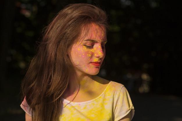 Zbliżenie portret pięknej brunetki pokrytej żółtą i różową farbą holi