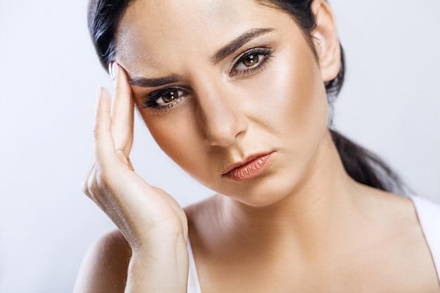 Zbliżenie portret pięknej chorej dziewczyny cierpiących na ból głowy