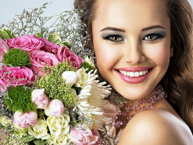 Zbliżenie portret pięknej dziewczyny szczęśliwy z kwiatami w ręce. młoda atrakcyjna kobieta trzyma bukiet wiosennych kwiatów