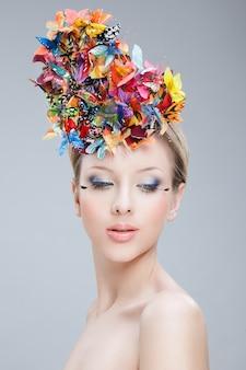 Zbliżenie portret pięknej dziewczyny z motylem z kwiatów i twórczego makijażu, na białym tle