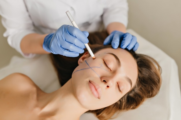 Zbliżenie portret pięknej kobiety podczas przygotowań do terapii kosmetologicznej w gabinecie kosmetycznym. profesjonalne zabiegi dermatologiczne, liftingi, odmładzanie