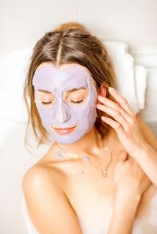 Zbliżenie portret pięknej kobiety w masce alginianowej na twarz leżącej na ręczniku