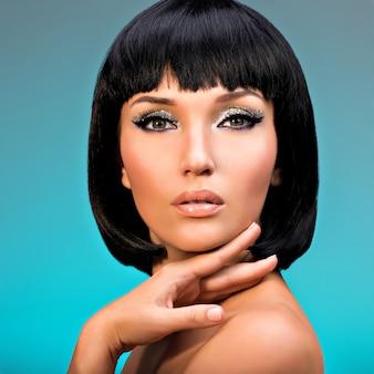 Zbliżenie portret pięknej kobiety z fryzurą bob. twarz modelki z kreatywnym makijażem