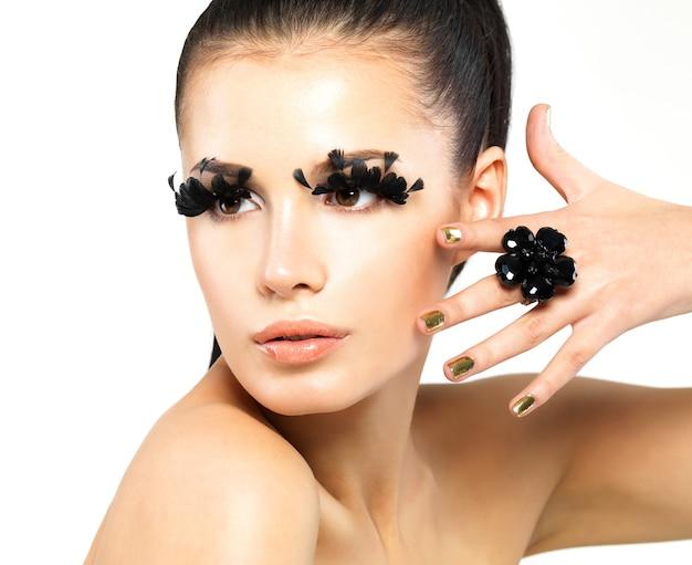 Zbliżenie portret pięknej kobiety z makijażem długie czarne rzęsy sztuczne i złote paznokcie.