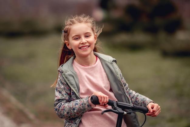 Zbliżenie portret pięknej małej dziewczynki, jazda na skuterze w parku