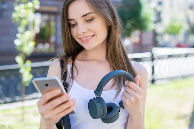 Zbliżenie portret pięknej marzycielskiej pozytywnej ładnej ładnej uroczej uroczej jej pani za pomocą gadżetu technicznego wybiera utwór z listy odtwarzania dzwoni do internetu trzymając szary pop popularne telefony do uszu