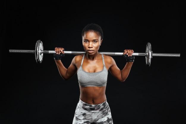 Zbliżenie portret pięknej młodej kobiety fitness ze sztangą na siłowni na białym tle na czarnej ścianie