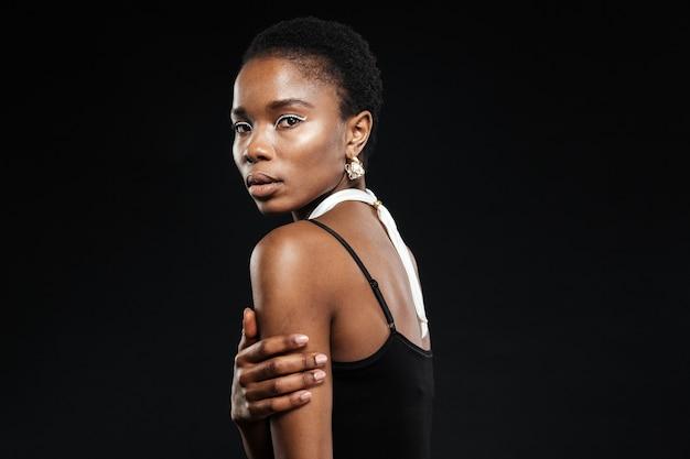 Zbliżenie portret pięknej młodej kobiety odizolowanej na czarnej ścianie