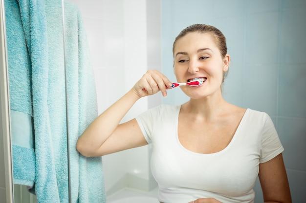 Zbliżenie portret pięknej młodej kobiety szczotkowanie zębów w łazience
