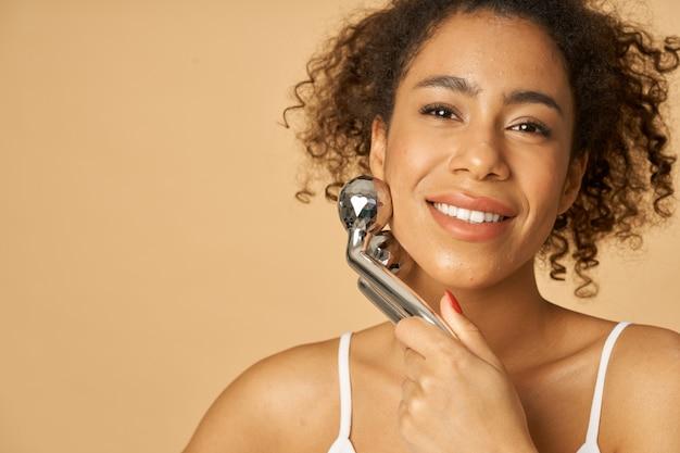 Zbliżenie portret pięknej młodej kobiety uśmiecha się do kamery podczas używania srebrnego metalowego wałka do twarzy