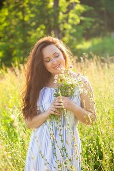 Zbliżenie portret pięknej młodej kobiety wąchania bukiet pięknych kwiatów w słoneczne lato