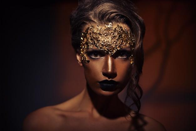 Zbliżenie portret pięknej młodej kobiety z kreatywnym makijażem i fryzurą na brązowym tle z cieniem drzewa