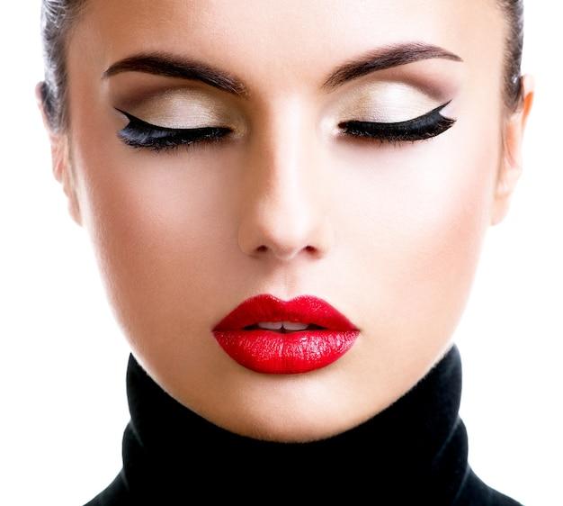 Zbliżenie portret pięknej młodej kobiety z makijaż moda pozowanie na białym tle.