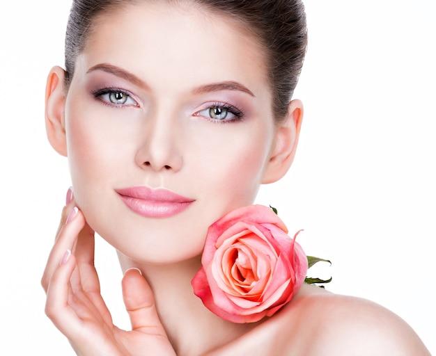Zbliżenie portret pięknej młodej kobiety ze zdrową skórą i kwiatem w pobliżu twarzy - na białym tle.