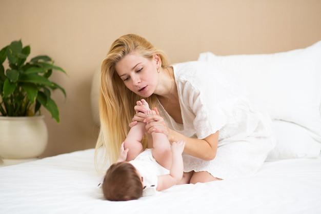 Zbliżenie portret pięknej młodej matki z długimi blond włosami przytulającej się z jej uroczym dzieckiem