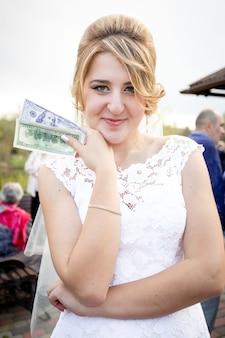 Zbliżenie portret pięknej narzeczonej trzymając paczkę pieniędzy