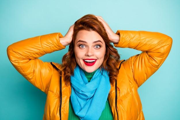 Zbliżenie portret pięknej pani śmieszne czerwone usta otwarte usta sezon zakupów ręce na głowie nosić żółty płaszcz niebieski szalik zielony golf.