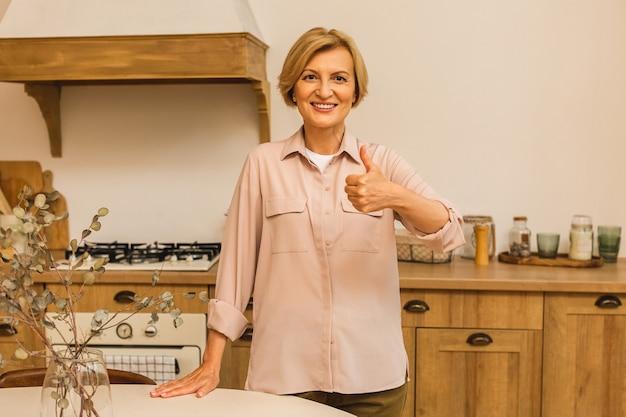 Zbliżenie portret pięknej starszej starszej starszej kobiety w wieku w kuchni po gotowaniu. kciuki w górę.