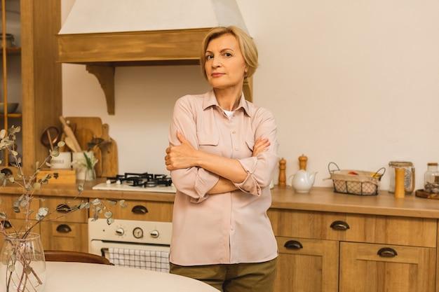Zbliżenie portret pięknej starszej starszej starszej kobiety w wieku w kuchni po gotowaniu.