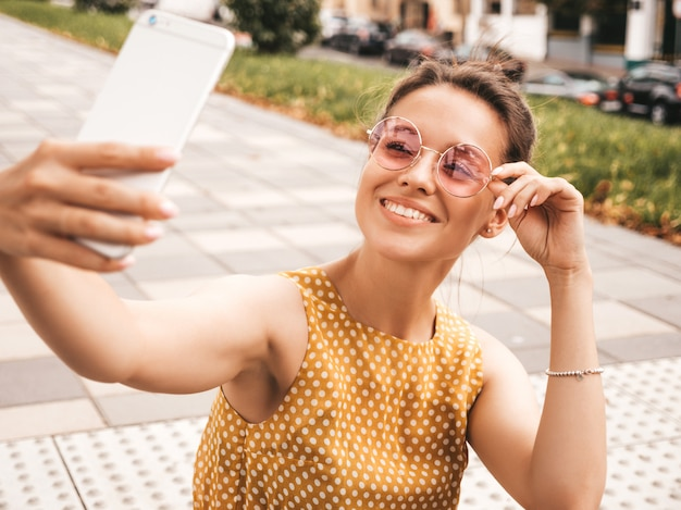Zbliżenie portret pięknej uśmiechnięte dziewczyny brunetka w lato hipster żółta sukienka. model robienia selfie na smartfonie. kobieta robienia zdjęć w ciepły słoneczny dzień na ulicy w okulary przeciwsłoneczne