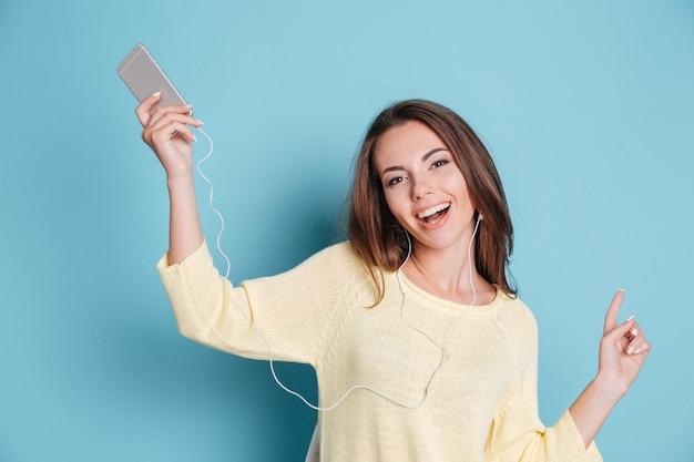 Zbliżenie Portret Pięknej Uśmiechniętej Młodej Kobiety Słuchającej Muzyki I Siedzącej Na Krześle Na Białym Tle Na Niebieskim Tle Premium Zdjęcia