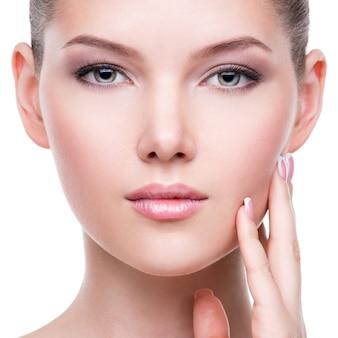 Zbliżenie portret pięknej zdrowej twarzy młodej całkiem białej kobiety z świeżą skórą - na białym tle.