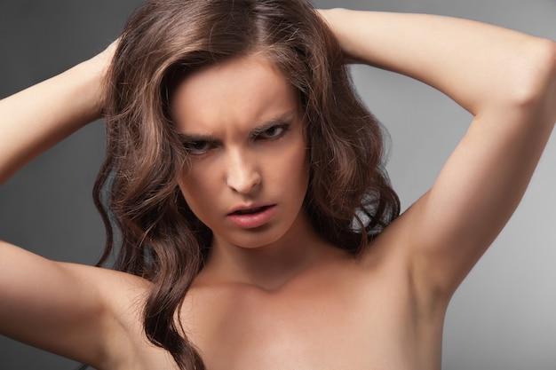 Zbliżenie portret poważnej damy z długimi kręconymi włosami na szarym tle