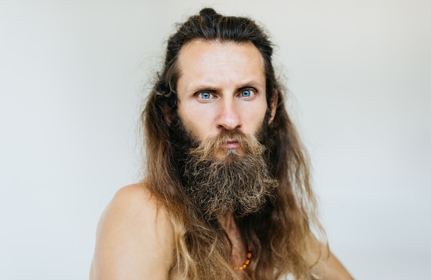 Zbliżenie portret poważny brodaty mężczyzna z emocjonalną twarzą, długie włosy i wąsy pozuje dla obrazków, odosobniony tło. hipster potrzebuje nowej fryzury