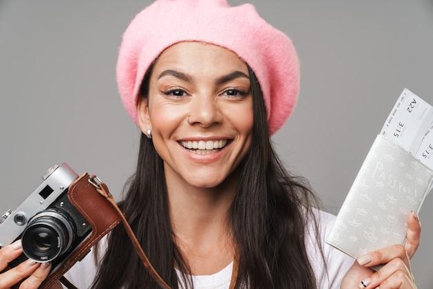 Zbliżenie portret przepięknej ładnej kobiety turystycznej w berecie, uśmiechając się, trzymając aparat retro i bilety podróżne na białym tle nad szarą ścianą