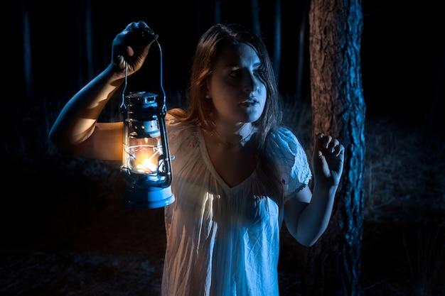 Zbliżenie portret przestraszonej kobiety zagubionej w lesie oświetlającej drogę z latarnią