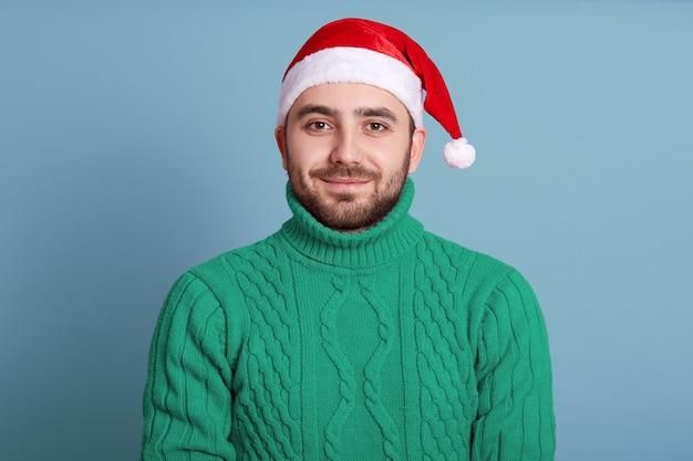 Zbliżenie portret przyjemny przystojny młody człowiek stojący na białym tle nad niebieskim, ubrany w zielony sweter i czerwony kapelusz świętego mikołaja, patrząc bezpośrednio. koncepcja atmosfery noworocznej.