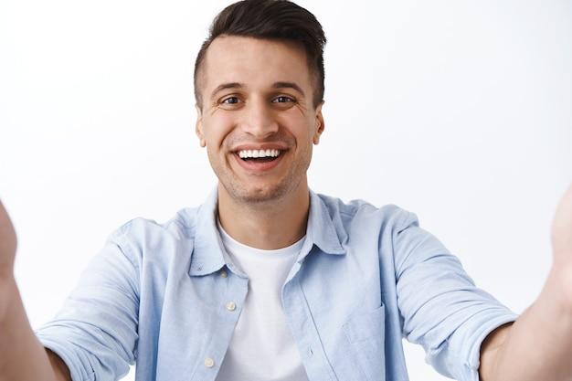 Zbliżenie portret przystojnego, miłego i przyjaznego, uśmiechniętego faceta z rodziny, biorącego selfie na tablecie, rozmawiającego z przyjaciółmi podczas wideoczatu podczas kwarantanny, pandemii koronawirusa, pozostającego online