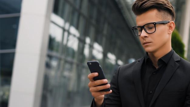 Zbliżenie portret przystojny biznesmen używa smartphone.