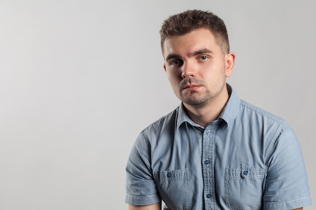 Zbliżenie portret przystojny nieszczęśliwy mężczyzna z złym nastrojem