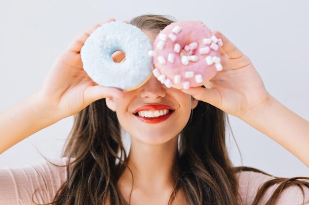 Zbliżenie portret radosna dziewczyna trzyma kolorowe pączki przed oczami. atrakcyjna młoda kobieta z długimi włosami, zabawy ze słodyczami, pyszne. jasne kolory, koncepcja diety, dieta.