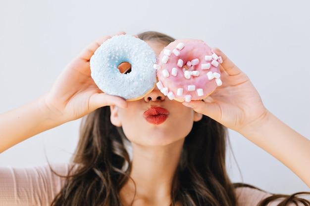 Zbliżenie portret radosna dziewczyna z czerwonymi ustami, zabawy z kolorowych pączków na oczach. atrakcyjna młoda kobieta z długimi włosami, trzymając słodycze. dobry nastrój, koncepcja diety, jaskrawe kolory.