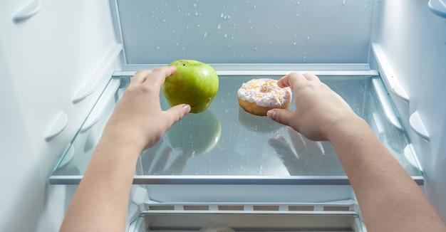 Zbliżenie portret rąk biorących zielone jabłko i pączek z lodówki