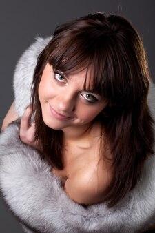 Zbliżenie portret rodzaju uroczej młodej dziewczyny z szare futro pozowanie