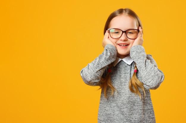 Zbliżenie portret rozochocona mała dziewczynka na żółtym tle