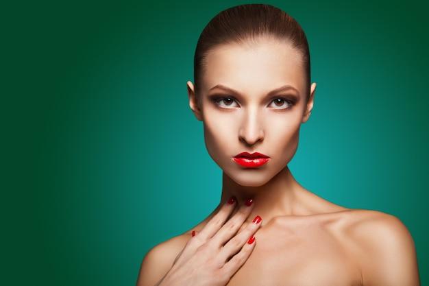 Zbliżenie portret seksownej kaukaskiej młodej kobiety z czerwonym makijażem glamour i jasnym manicure na zielonym tle