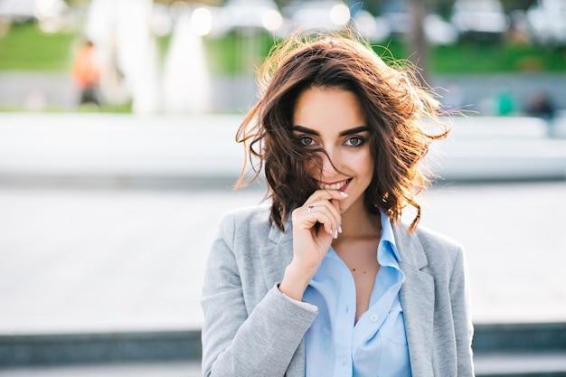 Zbliżenie portret śliczna brunetka dziewczyna z krótkimi włosami spaceru w mieście. nosi niebieską koszulę i szarą kurtkę. trzyma dłoń na ustach i uśmiecha się do kamery.