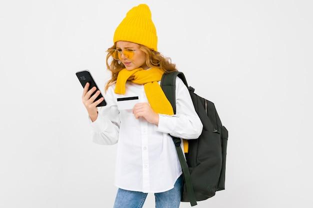 Zbliżenie portret śliczna caucasian nastolatek dziewczyna w zima szaliku i kapeluszu z telefonem i kredytową kartą na bielu