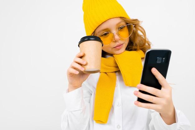 Zbliżenie portret śliczna caucasian nastolatek dziewczyna w zima szaliku z telefonem w jego ręce i papierową filiżanką na bielu i kapeluszu