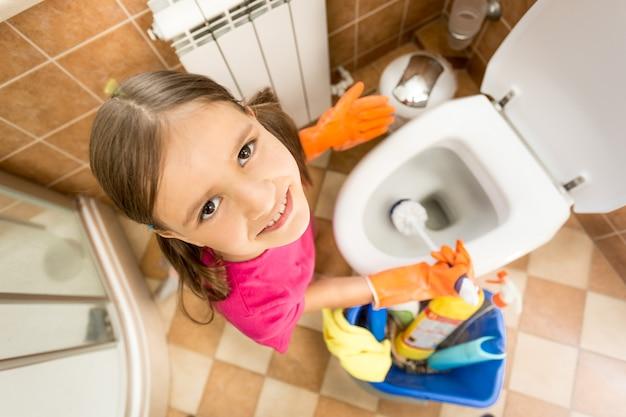 Zbliżenie portret ślicznej małej dziewczynki do czyszczenia toalety z pędzlem