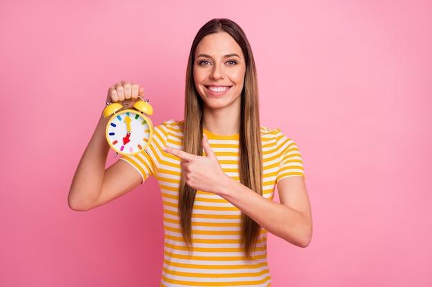 Zbliżenie portret ślicznej pewnie dziewczyny trzymającej demonstrujący retro zegar