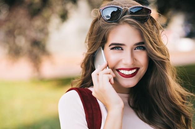 Zbliżenie portret słodkie dziewczyny z skutecznym makijażem i długimi włosami, mówiąc przez telefon w parku.