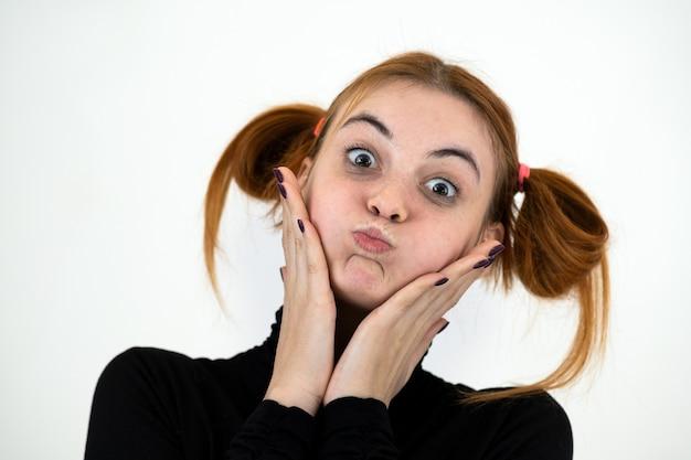 Zbliżenie portret śmiesznej rudzielec nastoletniej dziewczyny z dziecięcą fryzurą odizolowywającą na biel ścianie