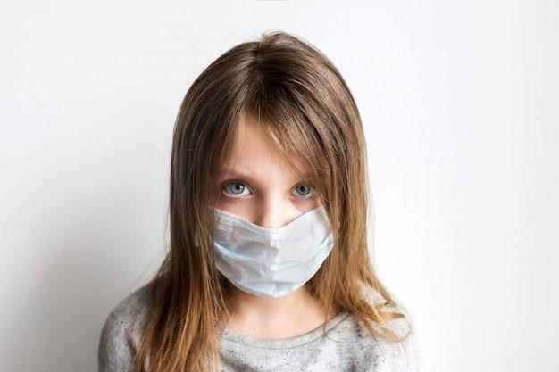 Zbliżenie portret smutnego dziecka w ochronnej masce medycznej patrząc