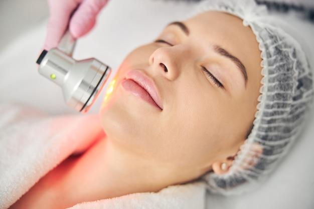 Zbliżenie portret spokojnej pacjentki z zamkniętymi oczami podczas zabiegu na skórę skin
